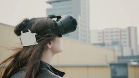 Het donkerbruine vrouwenmeisje met golvend haar gebruikt 3D Virtuele Werkelijkheidshoofdtelefoon op het dak 4K Stock Afbeelding