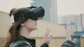 Het donkerbruine vrouwenmeisje met golvend haar gebruikt 3D Virtuele Werkelijkheidshoofdtelefoon op het dak 4K Stock Afbeeldingen