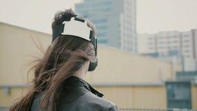 Het donkerbruine vrouwenmeisje met golvend haar gebruikt 3D Virtuele Werkelijkheidshoofdtelefoon op het dak 4K Stock Foto's