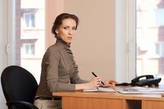 Het donkerbruine vrouwenwerk in het bureau, maakt nota's Stock Foto's