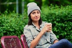 Het donkerbruine wijfje in een hoed drinkt koffie in een de zomerpark Royalty-vrije Stock Afbeelding
