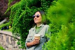 Het donkerbruine wijfje in zonnebril drinkt koffie in een de zomerpark Royalty-vrije Stock Foto
