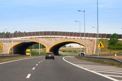 Het donkere auto drijven op de weg Zichtbare brug Stock Foto's