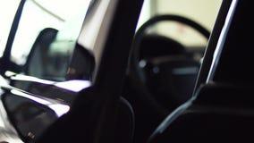 Het donkere Binnenland van de luxeauto - stuurwieldashboard voorraad Presentatie van de auto door de bestuurders` s deur stock video