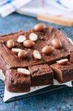 Het donkere die vierkant van de chocoladebrownie op een draadrek met crea wordt verfraaid Royalty-vrije Stock Afbeelding