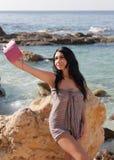 Het donkere haired meisje in sarongen maakt selfie tegen overzees royalty-vrije stock fotografie