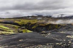 Het donkere landschap van IJsland met groen mos en zwarte weg, IJsland stock afbeelding