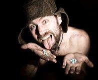 Het donkere portret van de enge kwade sinistere gebaarde mens met grijnslach, houdt in palm van een bos van pillen vreemde Russis Stock Fotografie
