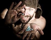 Het donkere portret van de enge kwade sinistere gebaarde mens met grijnslach, houdt in palm van een bos van pillen vreemde Russis Royalty-vrije Stock Foto