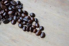 Het donkere zaad van de braadstukkoffie op houten raad Stock Foto's