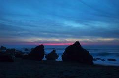 Het doordringen de Zonsondergang van het Strand Stock Foto