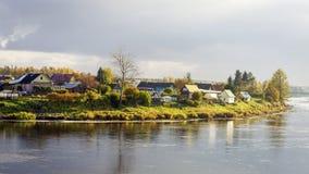 Het dorp aan de rivierkant in de herfst Stock Foto's