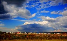 Het dorp bij de het plaatsen zon en hemel met onweerswolken Stock Afbeelding