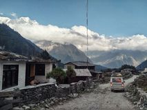 Het dorp in de kloof van de Kali Gandaki-rivier met hoge klippen en de vallei met lokaal vervoer en de sneeuw dekte pieken af stock afbeeldingen