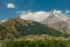 Het dorp Kazbegi en zet Kazbek in Georgië op Stock Afbeelding