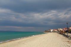 Het dorp op de kust van het turkooise overzees onder een donkere wolk Royalty-vrije Stock Afbeeldingen