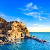 Het dorp, de rotsen en het overzees van Manarola bij zonsondergang. Cinque Terre, Italië Stock Fotografie