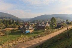 Het dorp wordt verlicht door de zon en de bergen zijn ver weg carpathians Stock Foto's