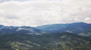 Het dorpslandschap van de bergvallei bewolkt stock afbeelding