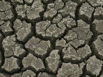 Het dorre land en de gebarsten grond die aan stukken wordt gebroken veroorzaken door de zonhitte stock afbeeldingen