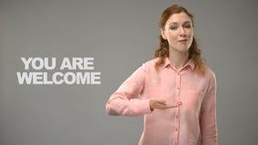 Het dove wijfje die u is welkom in asl, tekst op achtergrond, tolk zeggen stock video