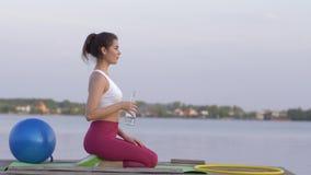 Het doven de dorst, jong gelukkig sportenmeisje drinkt mineraal duidelijk water van fles terwijl het doen van fitness en geniet b stock videobeelden