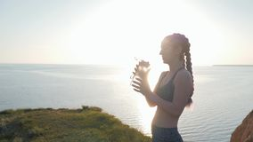 Het doven de dorst, mannetje geeft sportvrouwschudbeker met het drinken van mineraalwater na cardiotraining in heldere zonneschij stock footage