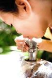 Het doven van het meisje dorst bij waterkoeler stock afbeeldingen