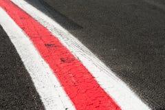 Het draaien van rode en witte lijnen op donker grijs asfalt Stock Foto's