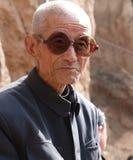 Het dragen van de donkere oude mens van glazenChina Stock Foto
