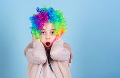 Het dragen van het dwaze clowngezicht Verraste kleine clown met geopende mond Het aanbiddelijke meisje helder gekleurd dragen royalty-vrije stock fotografie