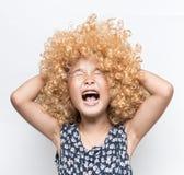 Het dragen van een blondepruik en een grappig gelaatsuitdrukking Aziatisch meisje royalty-vrije stock afbeelding