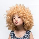 Het dragen van een blondepruik en een grappig gelaatsuitdrukking Aziatisch meisje stock afbeelding