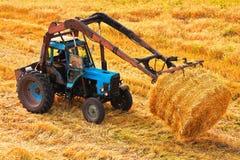 Het dragende hooi van de tractor bij gebied Stock Foto