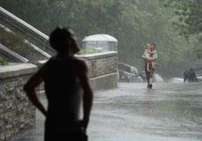 Het Dragende Meisje van de mens in de Regen Stock Afbeelding