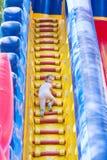 Het drie éénjarigenmeisje beklimt op een grote opblaasbare trampoline stock foto