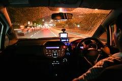 Het drijven door de regen in een stad bij nacht Stock Fotografie