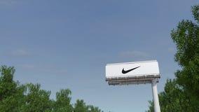 Het drijven naar de reclame van aanplakbord met de inschrijving en het embleem van Nike Het redactie 3D teruggeven Stock Fotografie