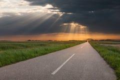 Het drijven op een lege landweg bij zonsondergang stock afbeelding