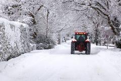 Het drijven van de tractor onderaan een sneeuw behandelde weg Stock Afbeelding