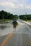 Het Drijven van de vrachtwagen op Overstroomde Weg stock afbeeldingen