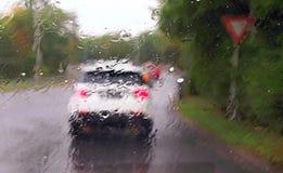 Het drijven van een auto in het regenonweer stock fotografie