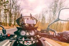 Het drijven van een motorfiets bij de lente bij de asfaltweg stock foto's