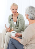 Het drinken van de arts met haar patiënt Stock Foto