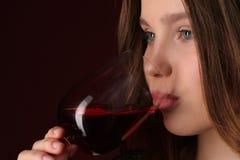 Het drinken van de dame wijn Sluit omhoog Donkerrode achtergrond Royalty-vrije Stock Afbeelding