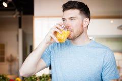 Het drinken van de mens jus d'orange stock fotografie