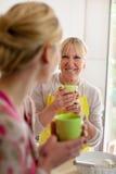 Het drinken van de moeder en van de dochter koffie in keuken royalty-vrije stock afbeeldingen