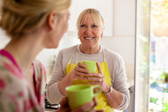 Het drinken van de moeder en van de dochter koffie in keuken stock fotografie