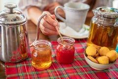Het drinken van de thee De vrouw eet eigengemaakte aardbeijam Theepot, honing, muffins op lijst Royalty-vrije Stock Afbeeldingen