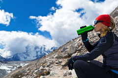 Het drinken van de vrouw in bergen Stock Foto's